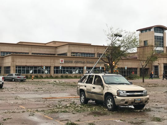 A damaged vehicle sits in front of the North Central Heart Institute at 7 a.m. Wednesday, Sept. 11, 2019, along 69th Street following a tornado that struck Tuesday night in southern Sioux Falls.