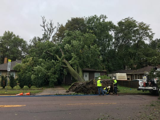 A crew repairs a gas line along Western Avenue that was damaged by an uprooted tree.