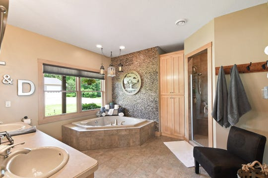 The en suite features a soaking tub, dual sinks and a walk-in shower.