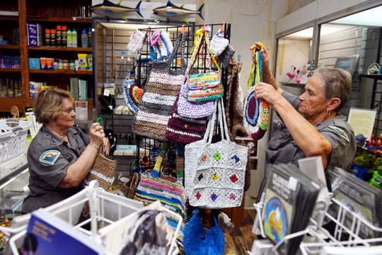 "Ethel Ford, left, and Nannette Wall hang their bags made of plastic grocery bags on a display in the gift shop of the Fishing Museum on Tuesday, Aug. 13, 2019 at the Sebastian Inlet State Park. Dubbed the ""Recycling Grannies"" by park staff, Ford and Wall were given space in the gift shop to sell their creations with all the proceeds going back to the park."