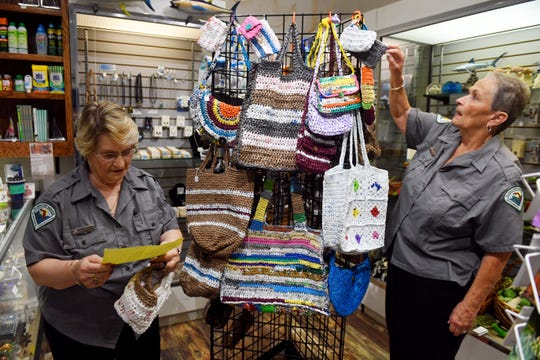 "Ethel Ford, left, and Nannette Wall hang their bags made of plastic grocery bags on a display in the gift shop of the Fishing Museum on Tuesday, Aug. 20, 2019 at the Sebastian Inlet State Park. Dubbed the ""Recycling Grannies"" by park staff, Ford and Wall were given space in the gift shop to sell their creations with all the proceeds going back to the park."