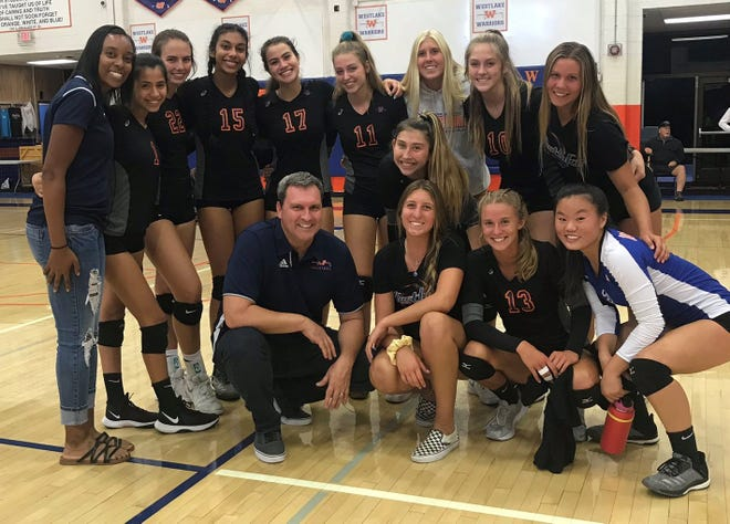 The Westlake High girls volleyball team poses for a picture after sweeping Newbury Park on Tuesday night, giving head coach Ernest Rittenhouse his 300th career victory at Westlake.