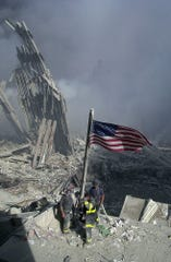 Firefighters raise an American flag at the World Trade Center after terrorists flew two planes into it, Sept. 11, 2001.