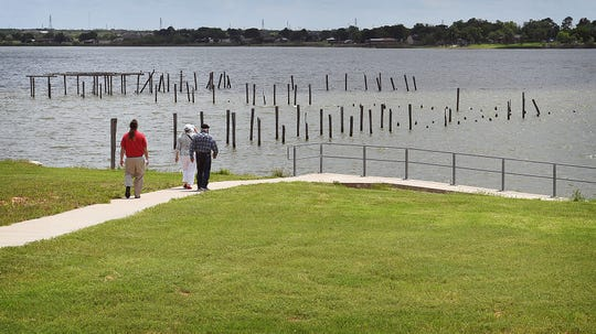 In this file photo, people attending the unveiling of a state historical marker at Lake Wichita in May walk down for a closer look where the former Lake Wichita Pavilion and scenic pier were located. Construction could begin in the next few months on a new boardwalk at this site.