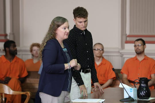 Lucas Collins and defense attorney Lisa Tome listen to the proceedings during his arraignment Wednesday in Muskingum County Common Pleas court.