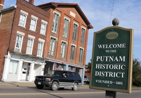 Traffic passes a pair of historic buildings on Putnam Avenue in Zanesville.
