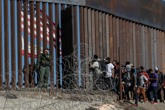Central American migrants look through a border fence as a U.S. Border Patrol agent stands guard near the El Chaparral border crossing in Tijuana, Mexico, on November 25, 2018.