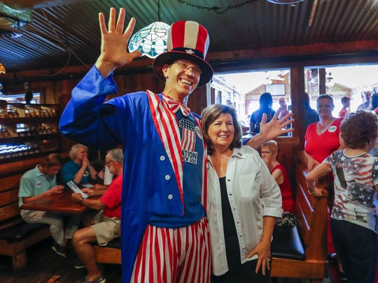 Rep. Karen Handel poses with a supporter dressed as Uncle Sam while participating in a get-out-the-vote rally at a restaurant in Marietta, Ga., on June 10, 2017.