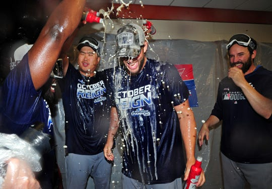 Dodgers pitcher Clayton Kershaw (middle) celebrates with pitcher Hyun-Jin Ryu (left) after clinching the NL West division.