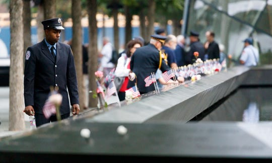 A firefighter walks past the South Pool during ceremonies at the National 9/11 Memorial marking the 18th anniversary of the September 11, 2001 terrorist attacks in New York.
