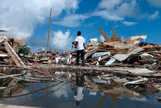 A man salvages debris in Marsh Harbour, Bahamas, on Sept. 10, 2019, one week after Hurricane Dorian.