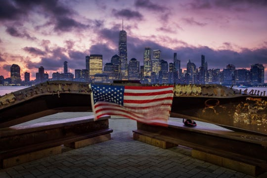 A U.S. flag hanging from a steel girder that was damaged in the Sept. 11 attacks on the World Trade Center blows in the breeze at a memorial in Jersey City, N.J., on the 18th anniversary of the terrorist attacks.