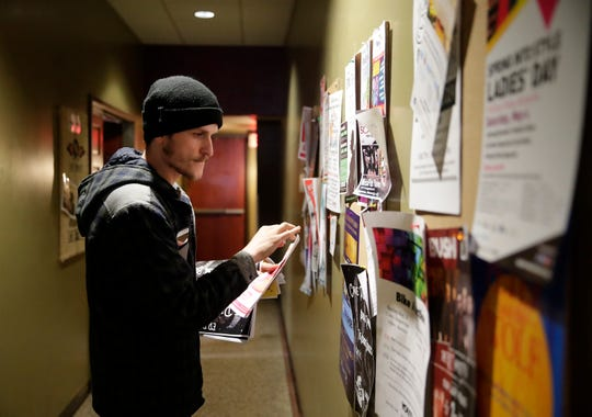 Levi Besaw puts up fliers at Copper Rock Coffee for upcoming shows at The Train Station on April 30, 2019, in Appleton, Wis.
