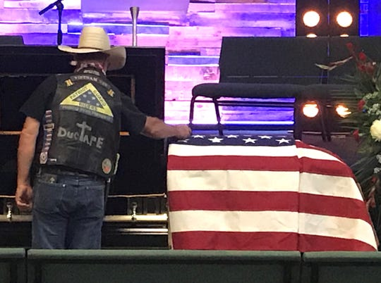 "Danny ""Duct tape"" Morris lays a quarter on the casket of Kameron Brown on Thursday at Victory Life Church in Brownwood. ""I'm a Vietnam vet. We'd always say to each other, 'If you need me, here's a quarter to call,'"" Morris said."