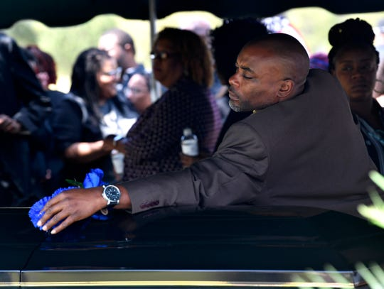 Carlos Washington, brother of Kameron Brown, places a blue flower on his brother's casket during graveside services in Early on Thursday.