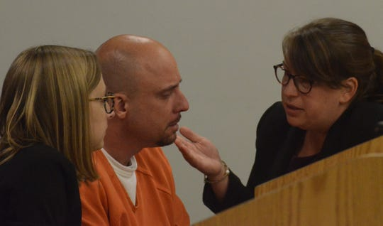 Attorneys Jessica Newton, left, and Eri VanCampen confer with John Loepke on Thursday.