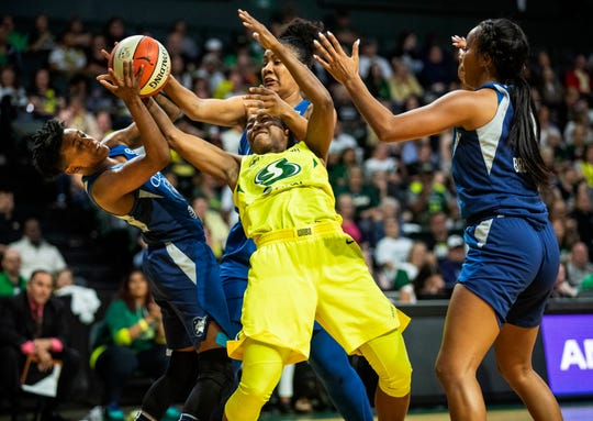 Seattle Storm's Jewell Loyd works between three Minnesota Lynx players during the first half of a WNBA basketball Western Conference semifinal, Wednesday in Everett. Loyd got off a shot and was fouled.