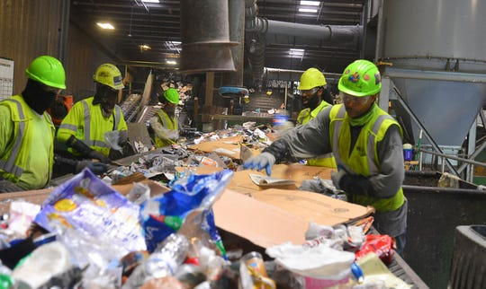 """Workers on the """"pre-sort line"""" grab items as they zip by on a conveyor belt at Waste Management Recycling Brevard in Cocoa."""