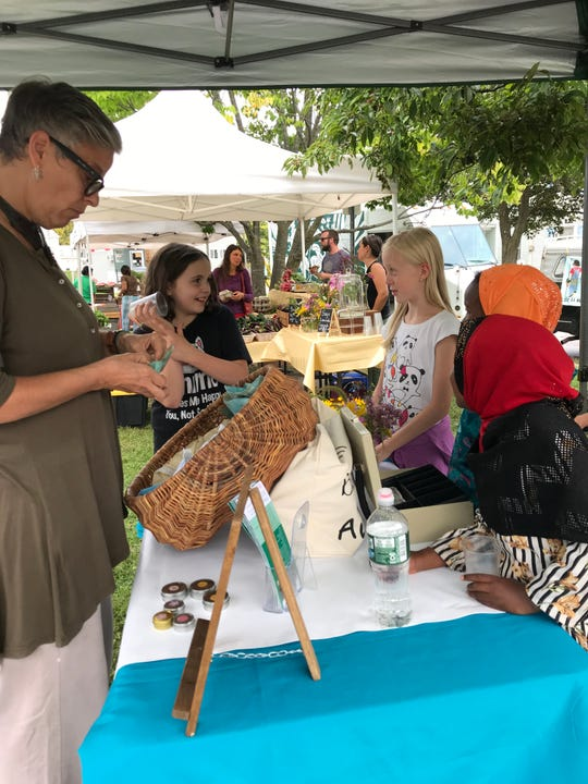 Susan Herrick, program coordinator with the Ethan Allen Residence, stands around the table with children from the Boys & Girls Club of Burlington at the Old North End Farmers Market. Sept. 10, 2019.
