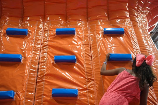Ten-year-old Youniq Le climbs at Amped Inflatapark, Tuesday, Sept. 10, 2019. The park has various bounce houses.
