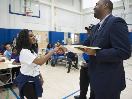 Then-Assemblyman Arthur Barclay hands an award to Unique Alford during an event at KIPP Cooper Norcross Academy in Camden in May 2016.