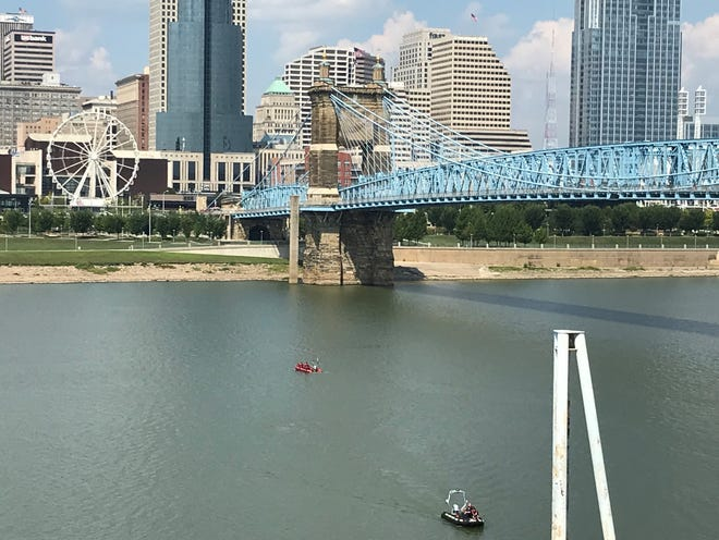 Search boats circle in the Ohio River in front of the Cincinnati skyline Thursday afternoon below the John A. Roebling Suspension Bridge for a person who reportedly jumped into the water. The pole in the foreground is the edge of the former Covington Landing boat mooring.