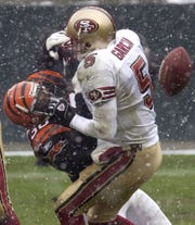 San Francisco 49ers quarterback Jeff Garcia (5) fumbles the ball as he is hit by Cincinnati Bengals defender Terrell Roberts (30) in the first half, Sunday, Dec. 14, 2003, in Cincinnati. Cincinnati recovered the fumble and ran it back for a touchdown. (AP Photo/Al Behrman)