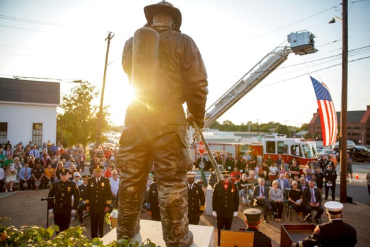 A statue of a firefighter stands overlooking the corner and all spectators in attendance during a 9/11 memorial ceremony at Clarksville Fire Rescue Station 1 in Clarksville, Tenn., on Wednesday, Sept. 11, 2019.