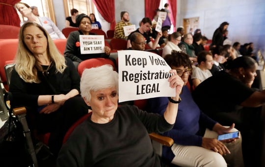 In this April 15, 2019, file photo, Suzanne Lanier, front left, holds up a sign in the House gallery as she and others oppose a bill pushed by the Tennessee Secretary of State that would impose new restrictions on groups that hold voter registration drives.