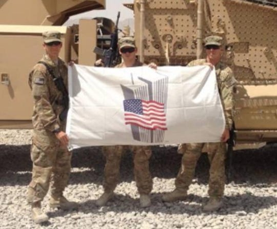 U.S. Army Staff Sergeant Robert Piano, left, holds Bob McKee's flag while stationed in Afghanistan.