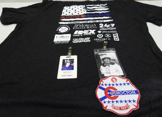 A T-shirt from the 9/11 Memorial Stair Climb in Columbus with badges honoring Angel Juarbe, a firefighter who died in the World Trade Center destruction, and Wilmer Hale, former chief of the Coshocton Fire Department who died in the line of duty in 1975.