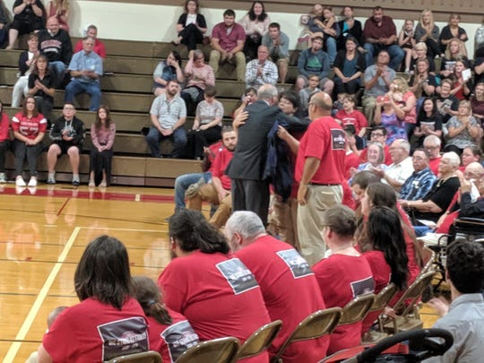 Jack Harbaugh, the father of Michigan football coach Jim Harbaugh, gives a U-M jersey to the Lasby family at Saranac High School.