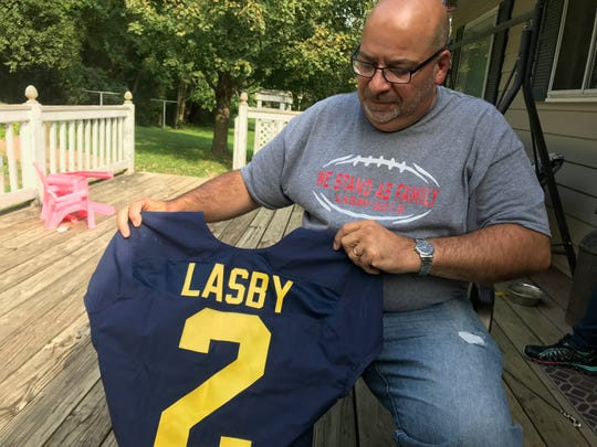 A look at the Michigan football jersey given to the Lasby family by Jack Harbaugh during the funeral for Skylar Lasby, held by Skylar's father, Scott.