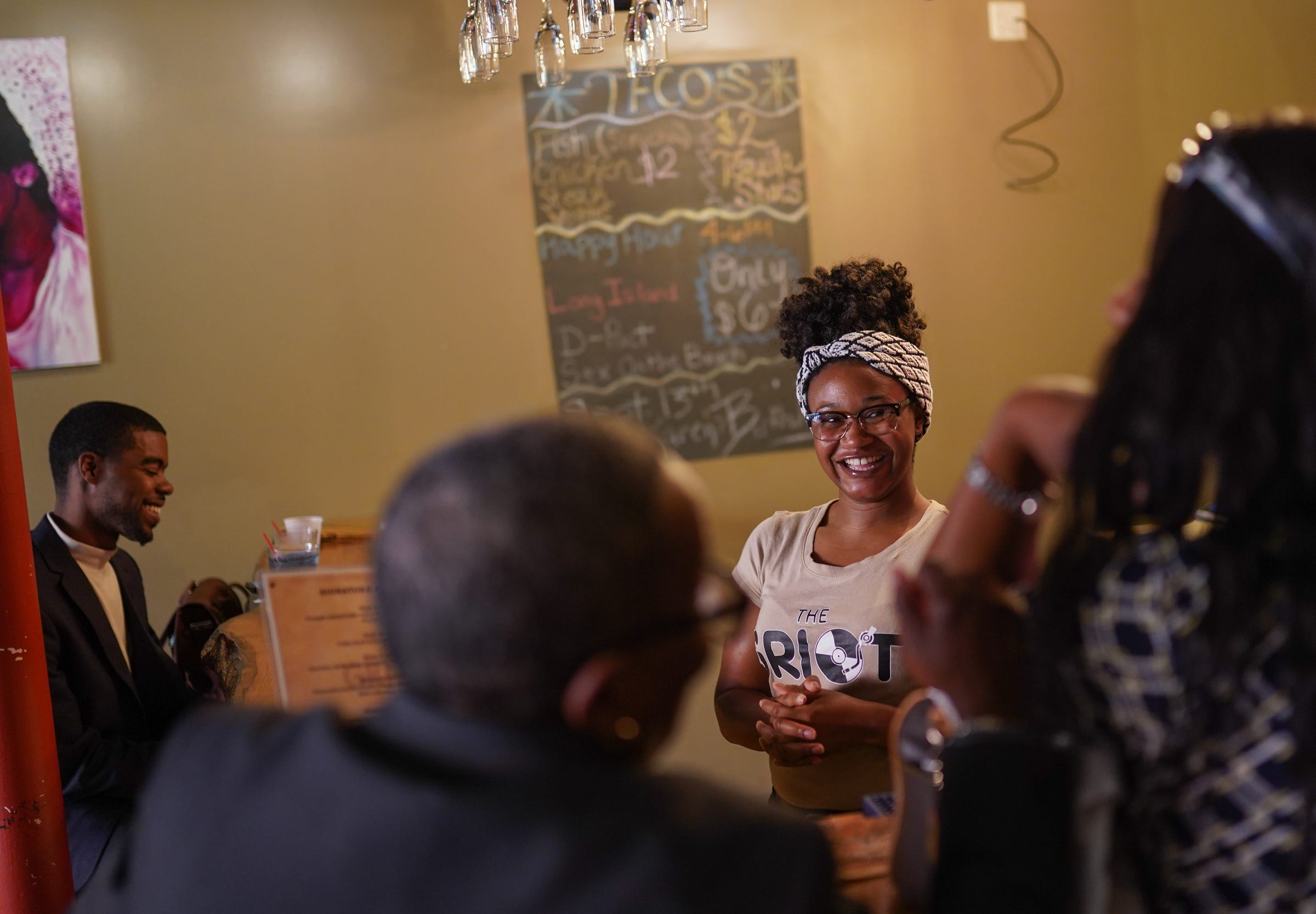 Wayne State University student DeLawren Bradshaw, who is working two part-time jobs to limit her student loan debt, talks with customers while bartending at Griot Music Lounge in Detroit on Tuesday, September 10, 2019.