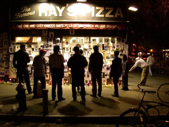 New Yorkers gather in front of Ray's Pizza in Manhattan on Saturday night, September 15, 2001, to look at flyers of missing person posted by family and friends of the victims of the World Trade Center building collapse.