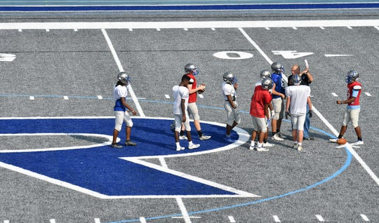 Athletic director and head coach Chris Westfall shows a play to Lincoln's players at their new gray turf field.