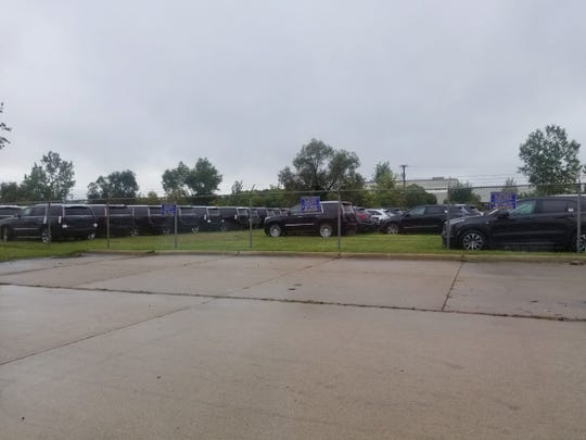 About 150 Cadillac crossovers and Escalade SUVs lined a fence along Grand River Avenue in Novi on Thursday.