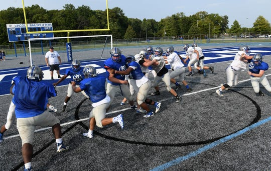 Lincoln players practice on their new gray turf field this week.