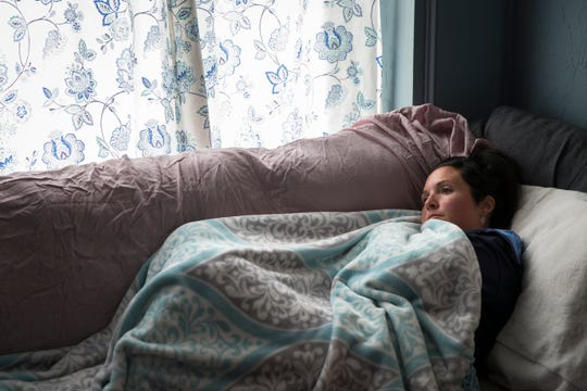 Alex Cellucci, 35, watches a movie at her home in Quincy, Mass., a day after having a tumor removed from behind her right eye.
