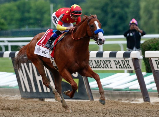 Justify, with jockey Mike Smith, crosses the finish line to win the 150th running of the Belmont Stakes and the Triple Crown on June 9, 2018.