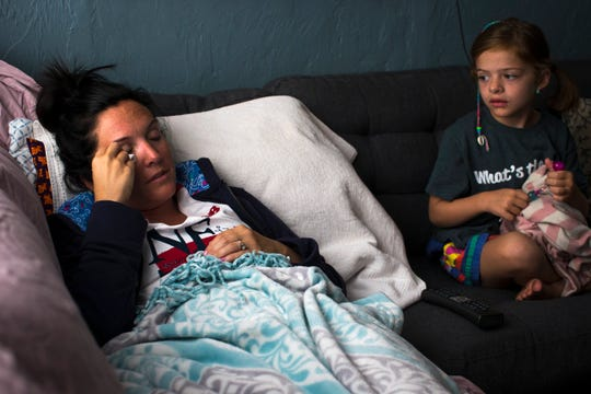 Alex Cellucci, 35, rubs fabric on her right eye, where she had a tumor removed the previous day, while watching a movie with her daughter, Maible, 6, at their home in Quincy, Mass. on Tuesday, Aug. 6, 2019. Alex and Maible both have neurofibromatosis, a genetic disorder that causes tumors to form on nerve tissue. Alex was diagnosed with neurofibromatosis type 2 at age 28 and has since endured two MRI scans every year to monitor tumors.