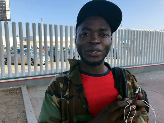 Ngoh Elliot Takere gives an interview in Tijuana, Mexico, where he has been waiting for two months to apply for asylum in the U.S., Thursday on the border with San Diego.