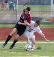 Elmira's Noah Sperduto (19) and Ithaca's Flynn McCarthy fight for possession  during the Express' 2-1 win in boys soccer Sept. 11, 2019 at Ernie Davis Academy's Marty Harrigan Athletic Field. Sperduto scored both Elmira goals and McCarthy scored for the Little Red.