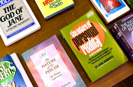 """Books by and about the late medium Jane Roberts on a table in the Elmira apartment where she channeled """"Seth."""" Decades later, Roberts and the teachings of Seth still have a worldwide following."""