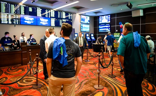 Gamers look at the odds board before making bets at the opening of the William Hill Sports Book at the Tropicana Evansville Thursday. The sports-book features a 16-by-9 feet video wall, ten 65-inch viewing monitors, and 12 odds boards, September 12, 2019.
