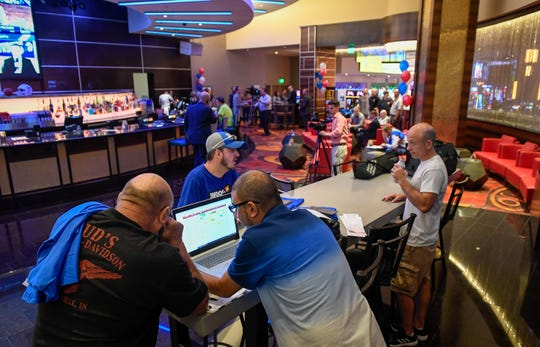Sports gamblers make their picks at the opening of the William Hill Sports Book at the Tropicana Evansville in Indiana on Sept. 12, 2019.