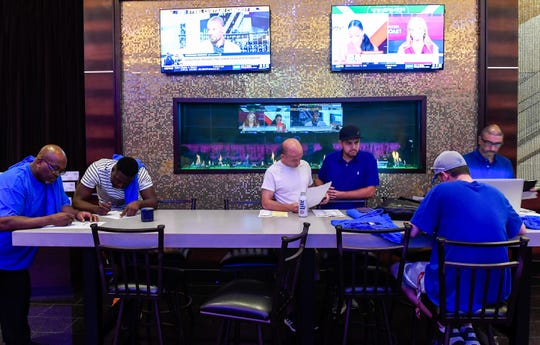 Gamers make their picks at the opening of the William Hill Sports Book at the Tropicana Evansville Thursday. The sports-book features a 16-by-9 feet video wall, ten 65-inch viewing monitors, and 12 odds boards, September 12, 2019.