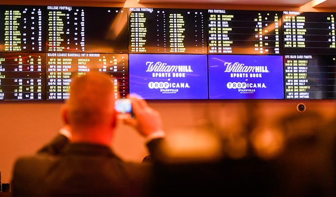 A patron takes a photo of the odds board at the opening of the William Hill Sports Book at the Tropicana Evansville Thursday. The sports-book features a 16-by-9 feet video wall, ten 65-inch viewing monitors, and 12 odds boards, September 12, 2019.