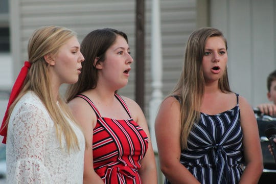 """Gibsonburg High School choir members Olivia Paul, pictured right, Amanda Rupke, and Emma Widmer sing """"God Bless America"""" Wednesday at the village's annual Sept. 11 ceremony."""