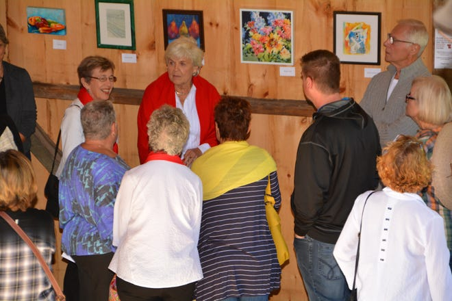 Bev Lisle and Joanne Dull, from left facing the camera, talk with guests as they look over art for sale at a past edition of ARTrageous. The benefit art sale for the Women's Fund of Door County returns Sept. 21 after a one-year absence.